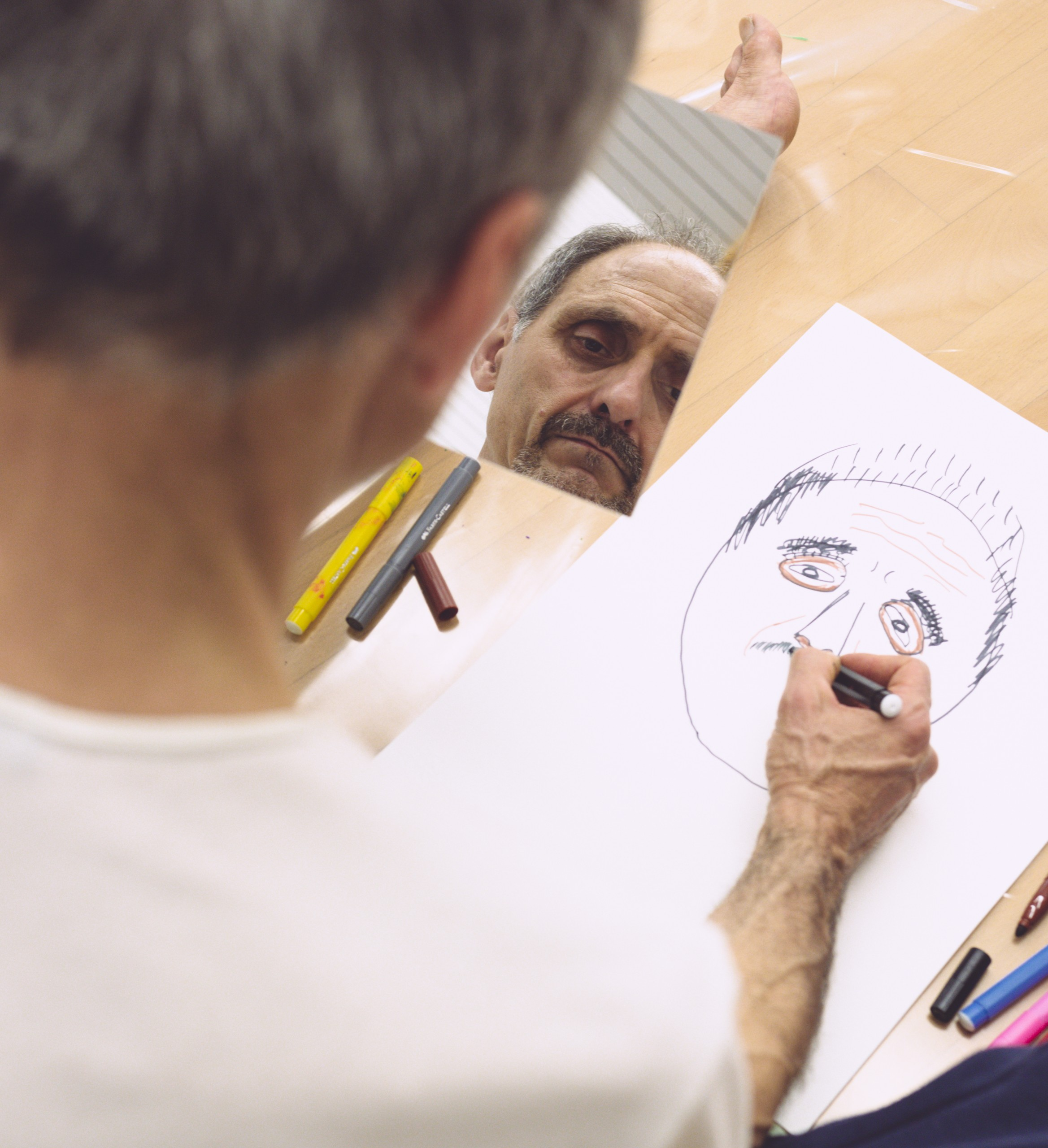 man drawing with mirror